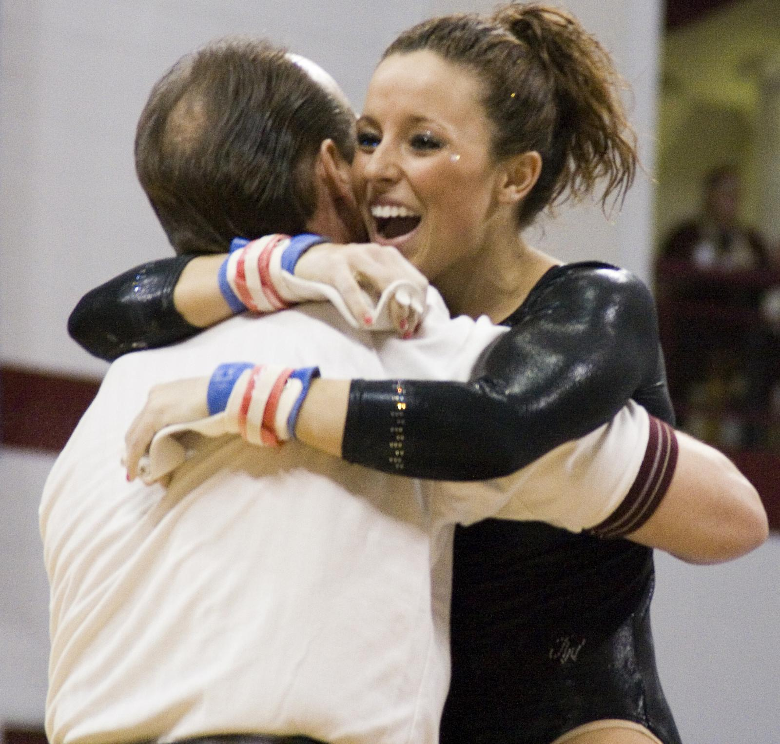 University of Minnesota women gymnastics player, Angela Walker hugs coach, Carmelina Carabajal, after she performs bar on Saturday at the University of Minnesota Pavilion.