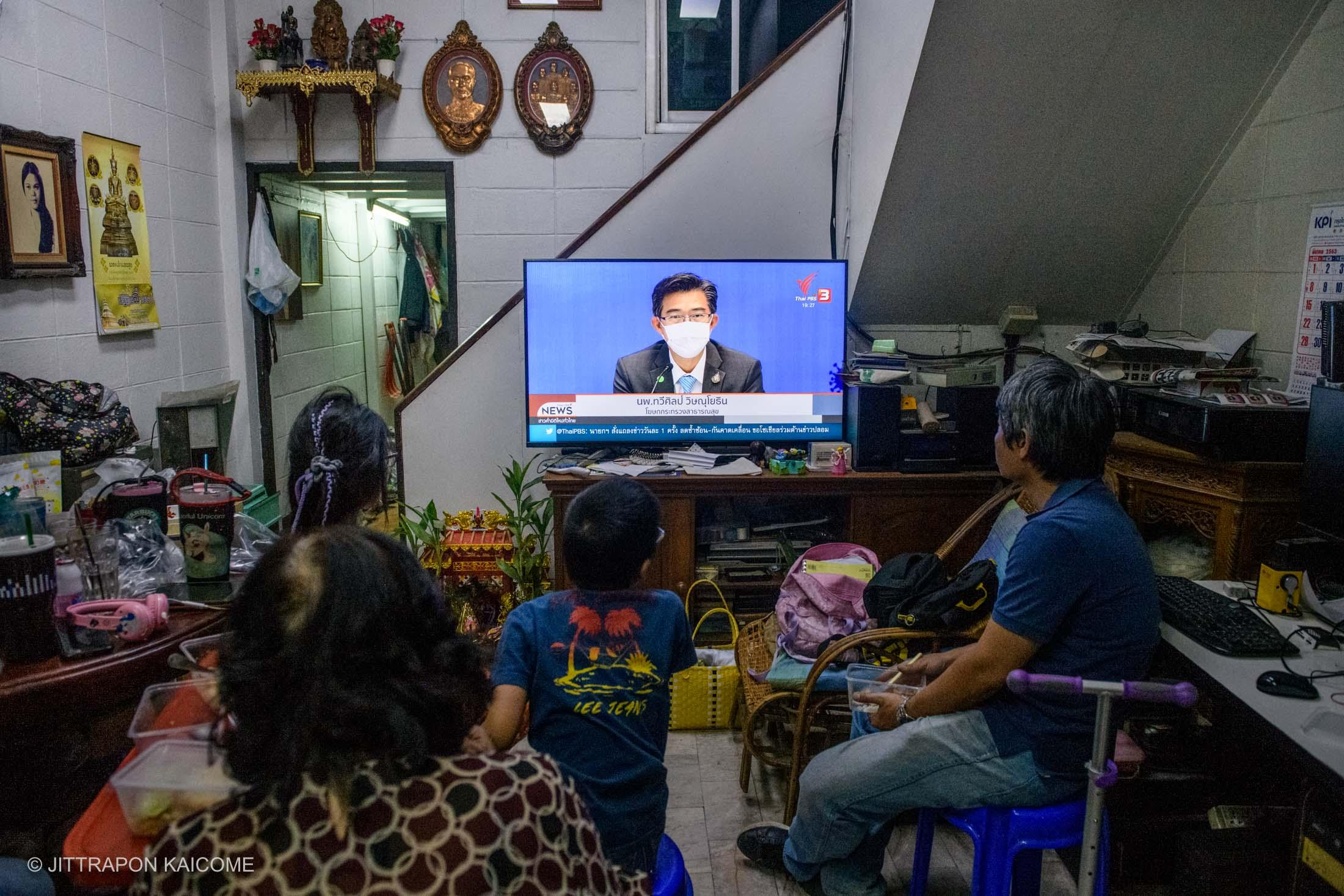 07.25 PM - Social distancing keep people isolated at home, a Chinese-Thai family in Chiang Mai gathered at the living room watching press-release on the coronavirus measure by Thai Ministry of Public Health. Chiang Mai, Thailand in March 25, 2020.