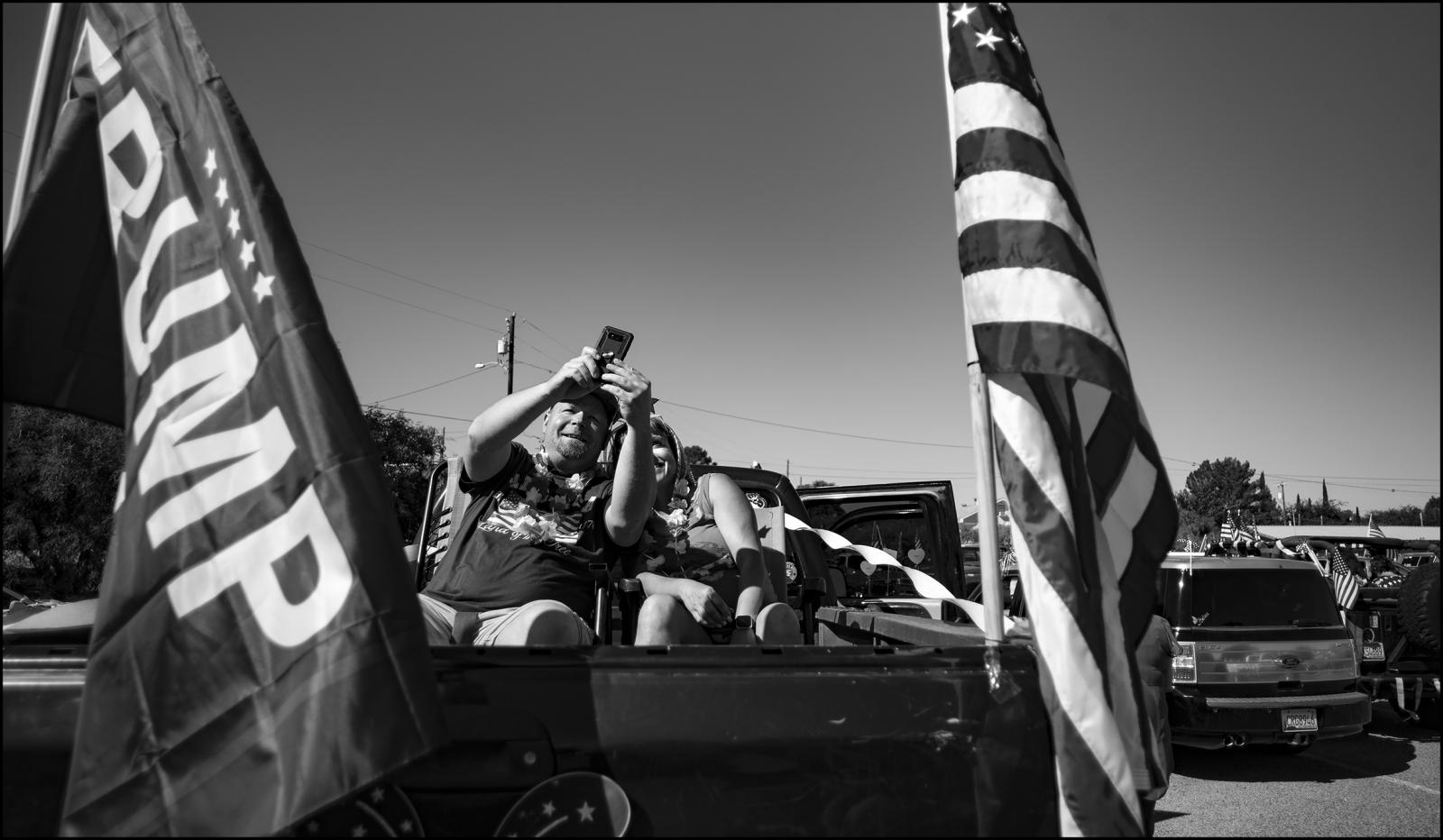 """Sitting in the bed of their pickup, a couple await the start of """"rougue"""" parade held in Benson, AZ. USA. Population 5000, 4th of July morning, 2020. A form of protest, this vehicular parade drew close to 500 people, not social distancing or using protective measures against COVID-19. Benson, Arizona. 07/04/2020."""