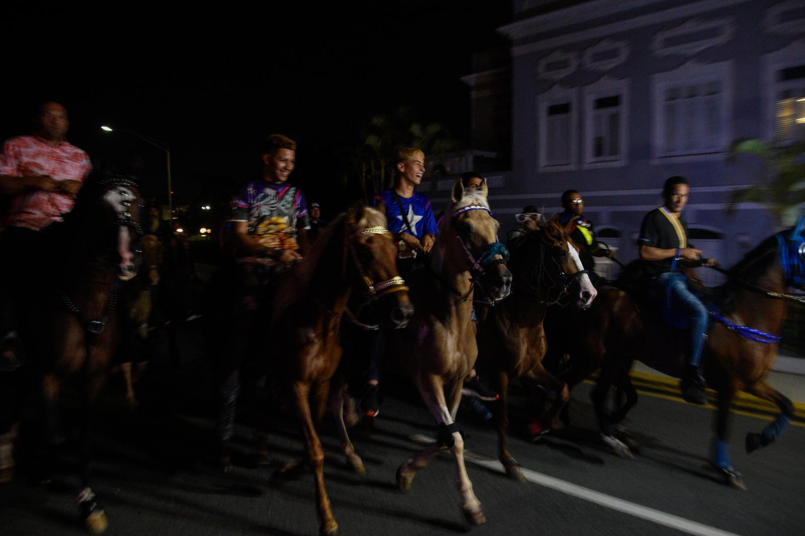 """Demonstrators join the march on horses, what is called on the island a """"cabalgata"""" during the seventh day of protest calling for the resignation of Governor Ricardo Rossello."""