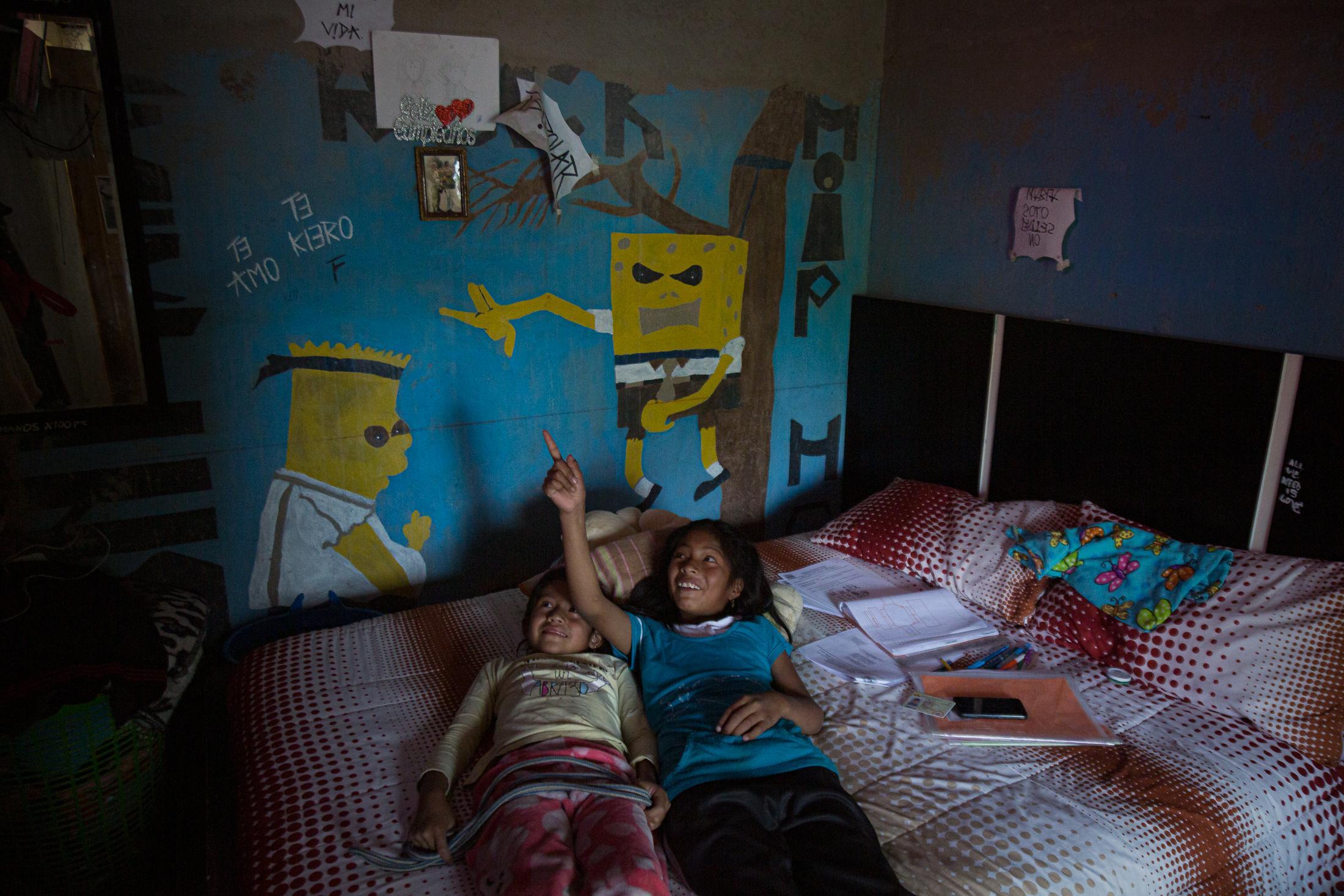 Analí Caiza (6) acompaña a su prima, Celina Paucar (12), en casa de su abuela, después que ella hace su tarea. Ellas miran televisión y juegan en la habitación de sus tíos cuando Celina termina los deberes que su escuela le envía a través de Whatsapp, en la tarde del 22 de mayo de 2020. Cotogchoa-Ecuador. Andrés Yépez.