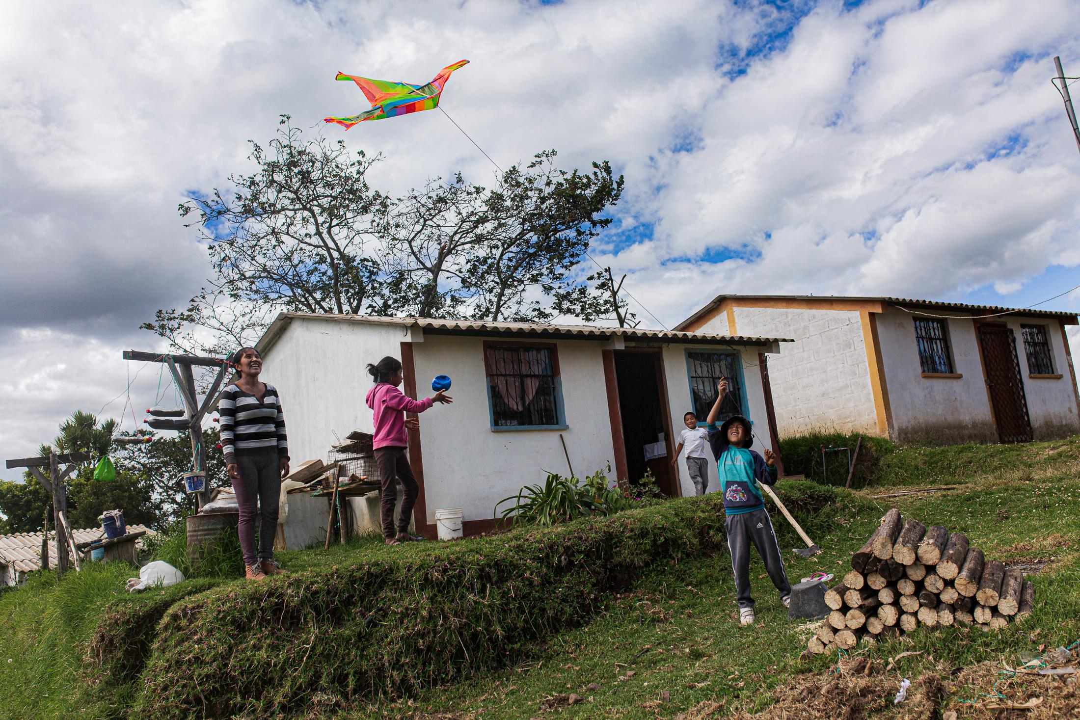 Sandra Guallichico (32) junto con sus hijos Celina (12), César (8) y Francisco (11) pasan parte de su día afuera de casa, jugando, cuidando sus sembríos. Cuando el clima lo permite les gusta salir a volar cometa. 26 de mayo de 2020. Cotogchoa-Ecuador. Andrés Yépez. La cotidianidad en las zonas rurales ha sido afectada de diferente manera que en las zonas urbanas. Su confinamiento no se limita a estar dentro de casa. El campo es parte de su casa.