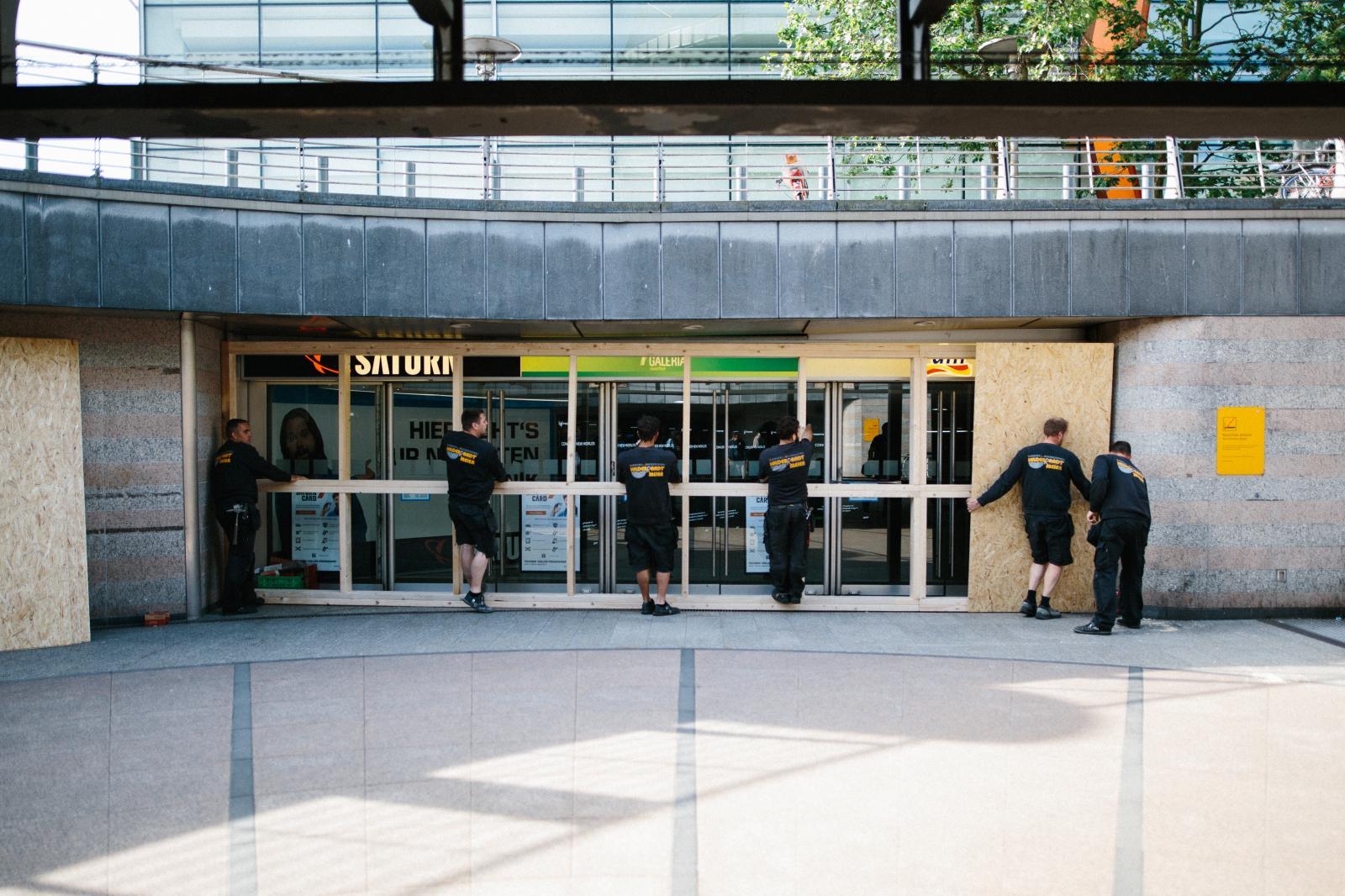 Arbeiter vernageln Scheiben von Kaufhof in Befürchtung von Auschreitungen.