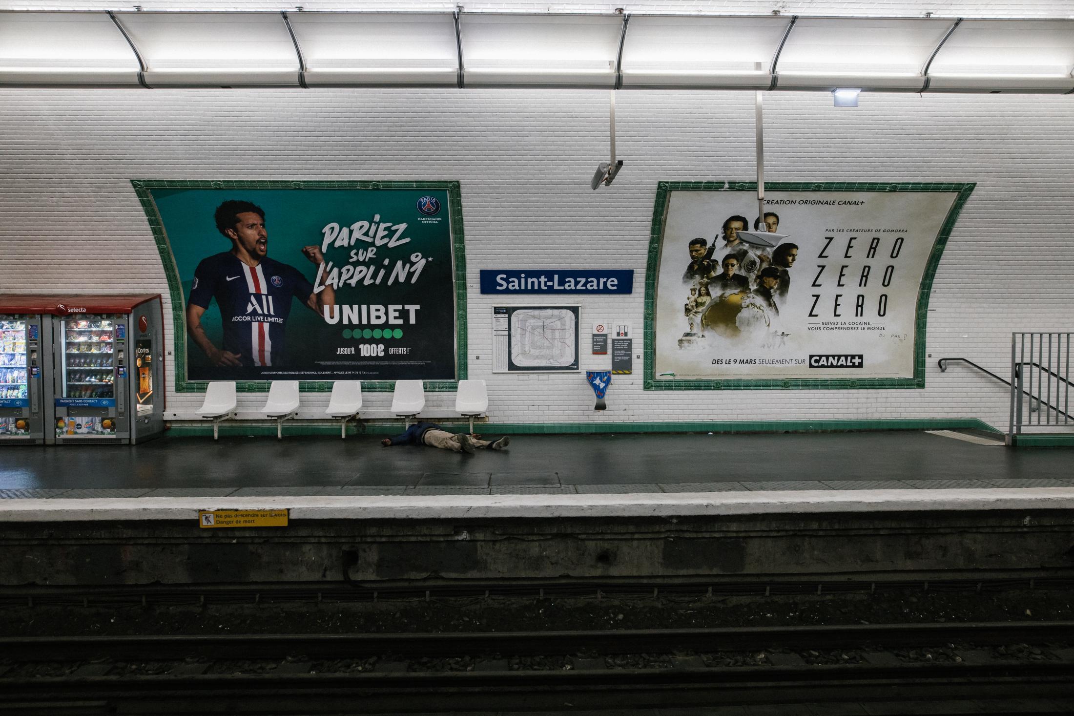 Paris, gare Saint Lazare, le 5 avril 2020. Un sdf dort sur le quai vide. Avec le confinement, les sdf n'ont presque plus de revenus et ont de grandes difficultés à se nourrir. L'homme va se réveiller quelques minutes plus tard et monter dans le métro.