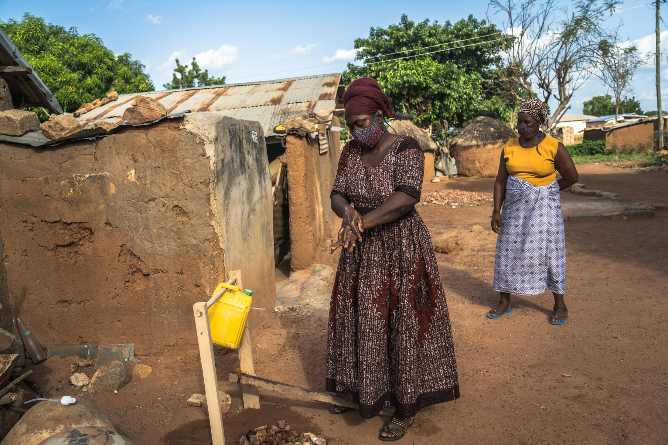 "Women from Kperiga community queue to wash their hands using ""tippy tap"" handwashing system introduced by CRS ICOWASH project while practicing social distancing and wearing face masks during the Covid-19 pandemic in Kperiga, Northern Ghana on June 15, 2020."