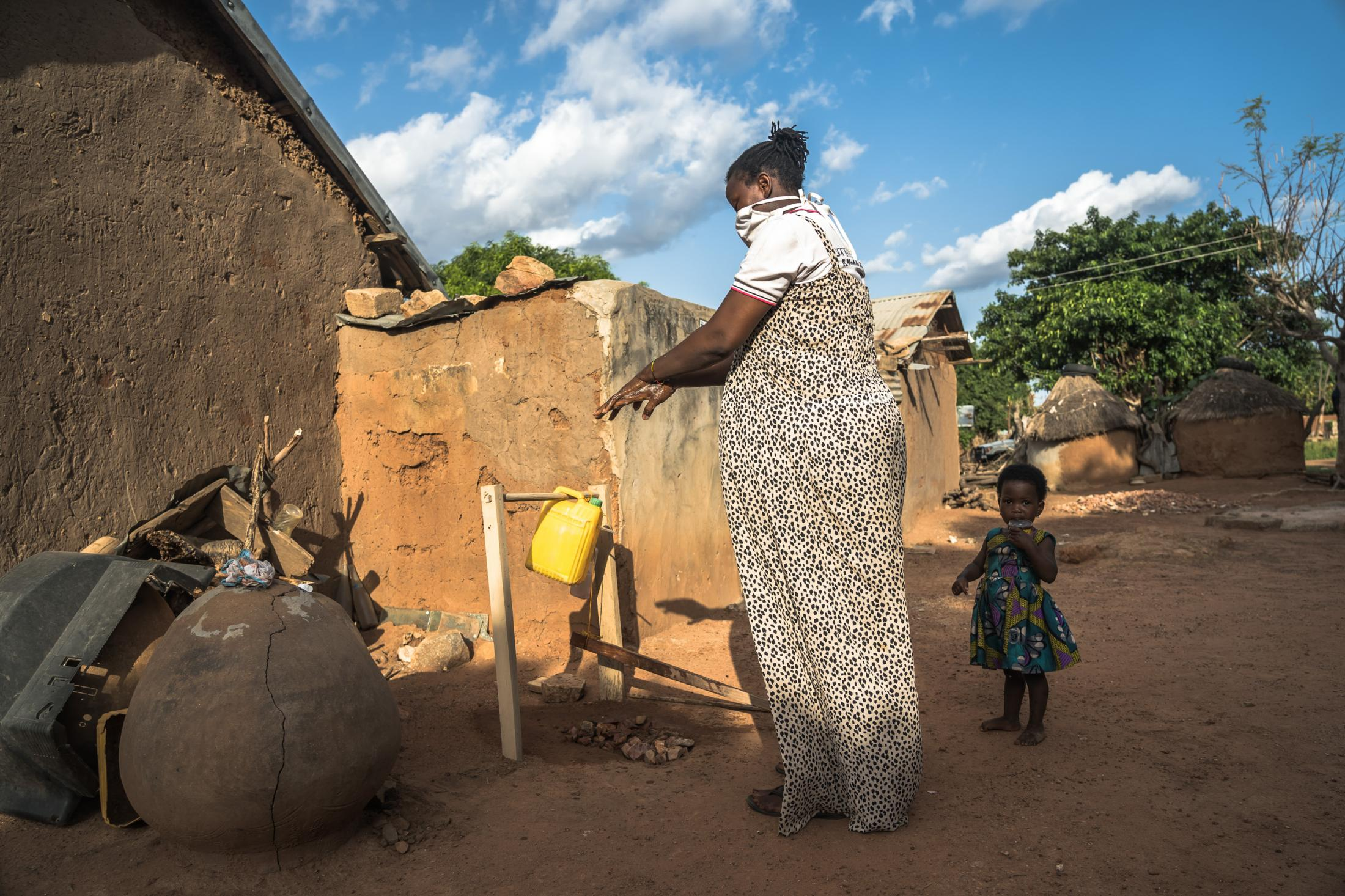 "Cynthia Akanyako (28) washes her hands using the ""tippy tap"" handwashing system introduced by CRS ICOWASH project during the Covid-19 pandemic in Kperiga, Northern Ghana on June 15, 2020."