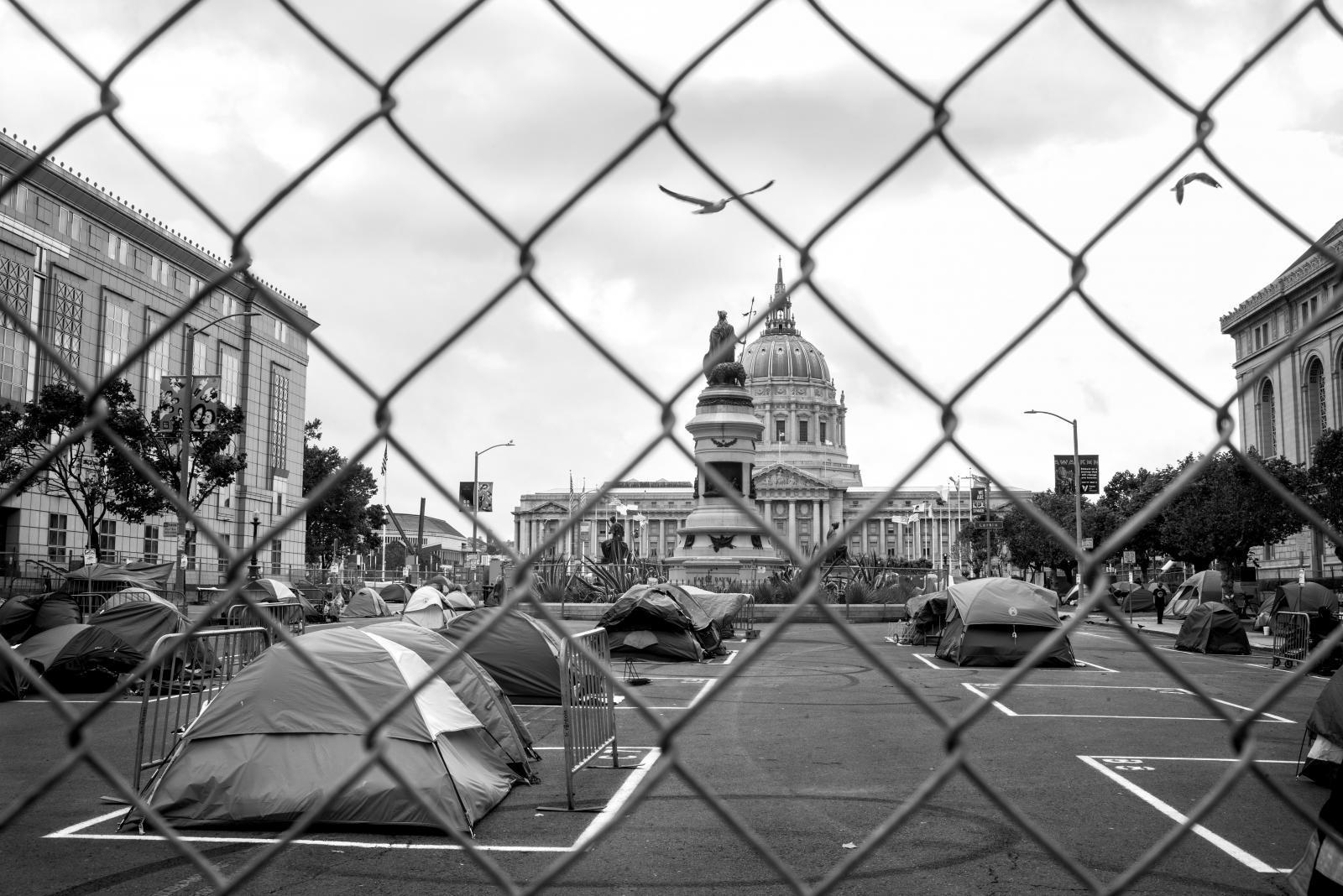 Darcy Padilla / Una residente de San Francisco, Darcy Padilla regresó a su hogar en una ciudad encerrada. La primera ciudad en los Estados Unidos en confinarse en un lugar que todavía se está reabriendo lentamente. Luchando contra el instinto de acercarse, ella fotografía desde la distancia. Residentes que atraviesan el nuevo paisaje. Calles sin tráfico, edificios tapiados y parques llenos de gente son el telón de fondo de la angustiosa experiencia de vivir entre el acercamiento y la separacion.   ----------------------------------------------------------  A longtime resident of San Francisco, Darcy Padilla returned home to a city in lockdown. The first city in the United States to shelter in place that is still slowly reopening. Fighting the instinct to get close, she photographs from a distance.  Residents traversing the new landscape. Streets with no traffic, boarded up buildings and crowded parks are the backdrop for the distressing experience of living between access and separation.