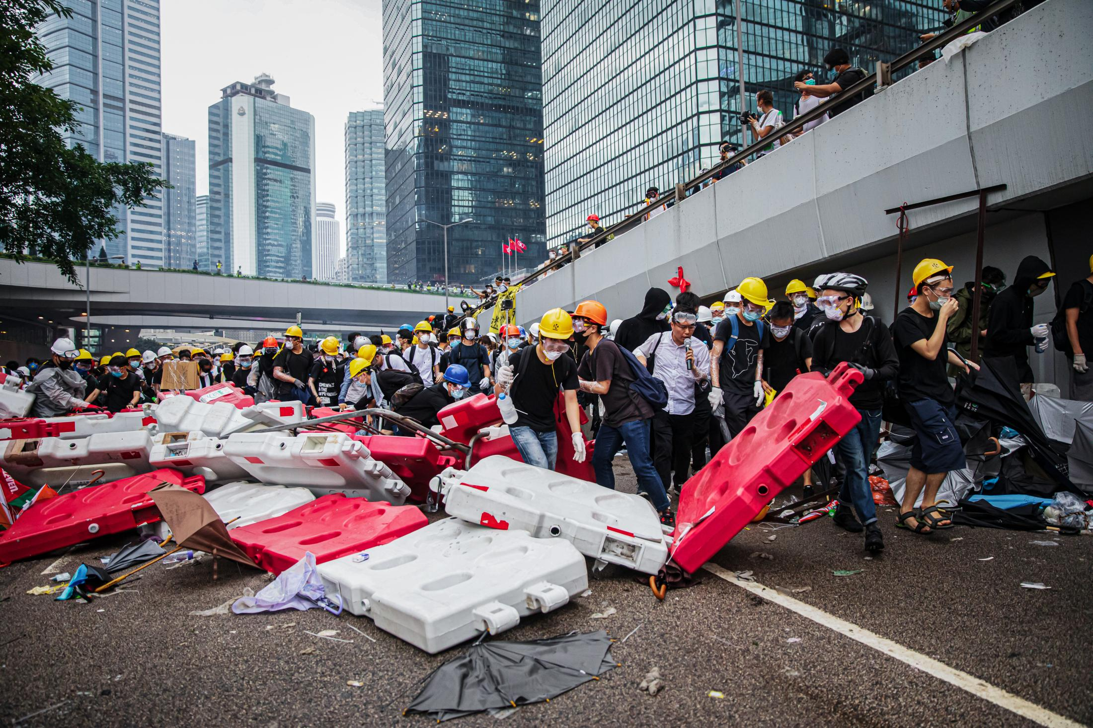 Protesters break down protective barriers to escape a police charge on Harcourt Road, near LegCo. On June 12, there were about half a million people on the streets in a protest that surrounded LegCo to prevent deputies from entering to discuss the extradition bill. Law enforcement officials respond with batons, pepper spray and tear gas to disperse the protesters.