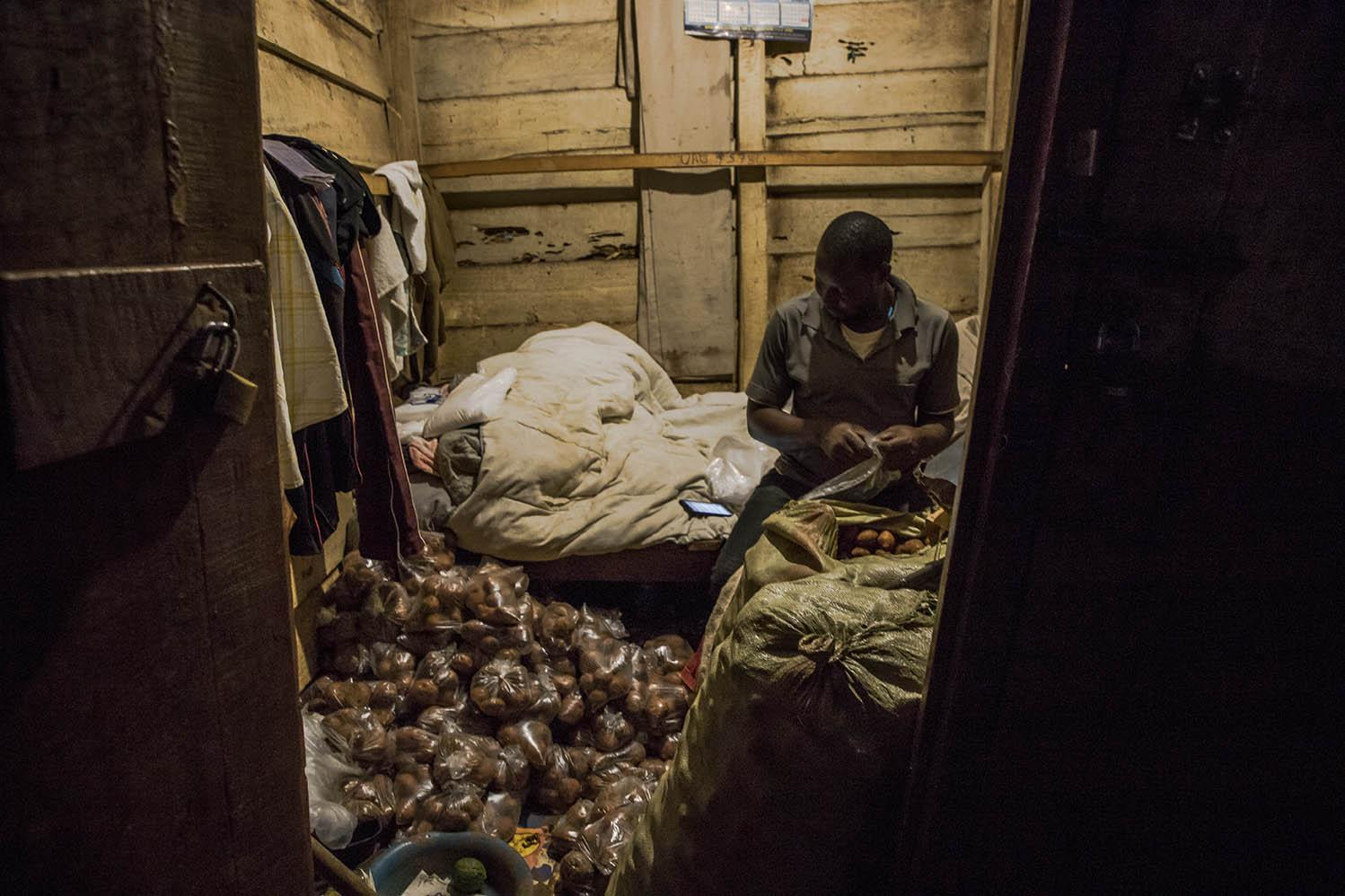 Kasule Francis, a famous Nakawa Market vendor in Kampala, Uganda, prepares and packs Irish potatoes in small polythene bags on 7 April 2020. Due to the COVID-19 pandemic, what used to be his food store is now a sleeping room and stock collection area.