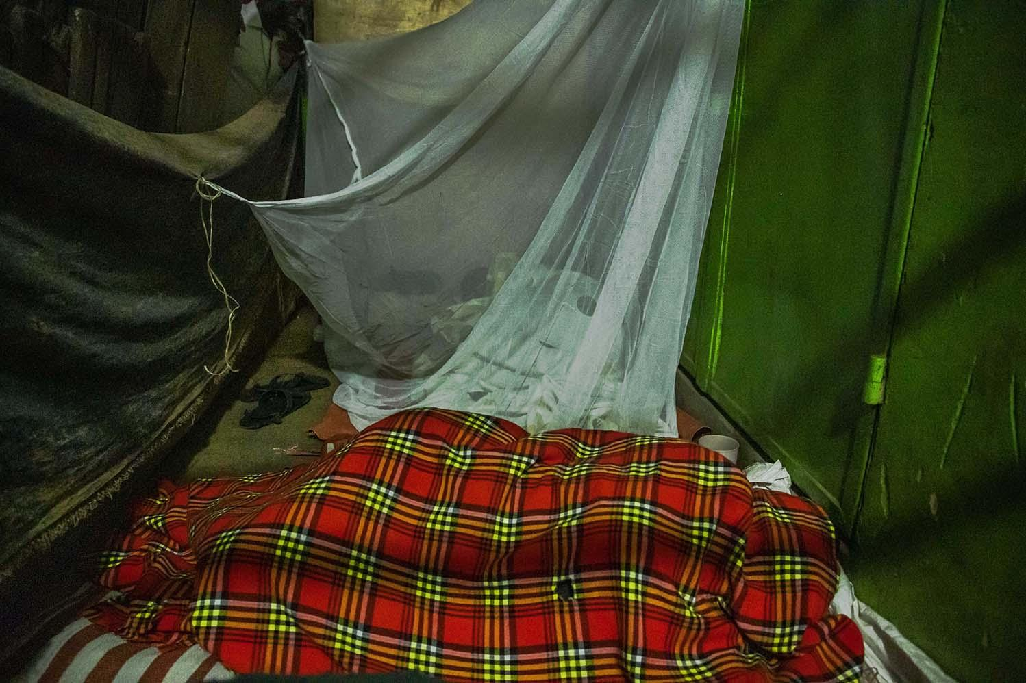 A mother sleeping beside her child in a mosquito net by a veranda at the Nakawa Market in Kampala. Many single mothers in the market have resorted to staying with their young ones because they do not have anyone maturely responsible to look after them while they work.