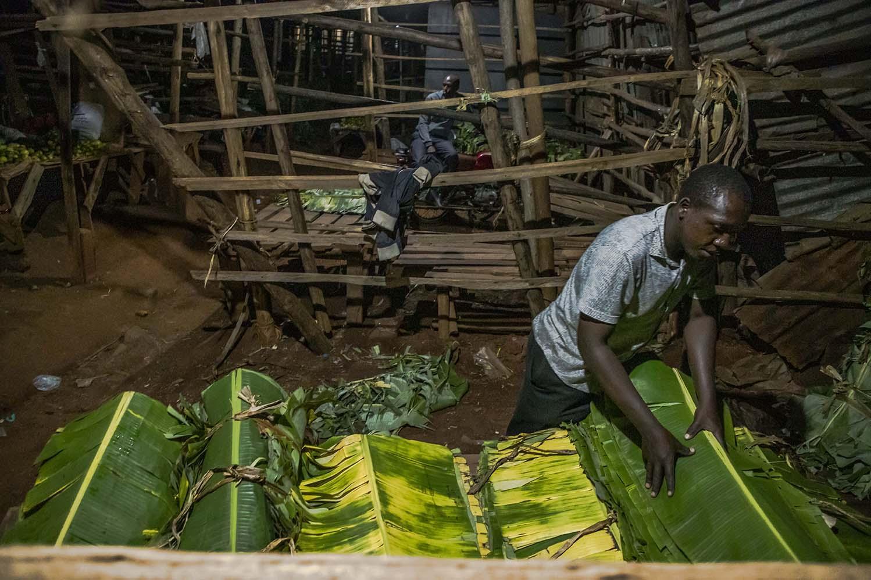 A vendor at Nakawa Market organizes banana leaves at his stall before he gets to sleep.