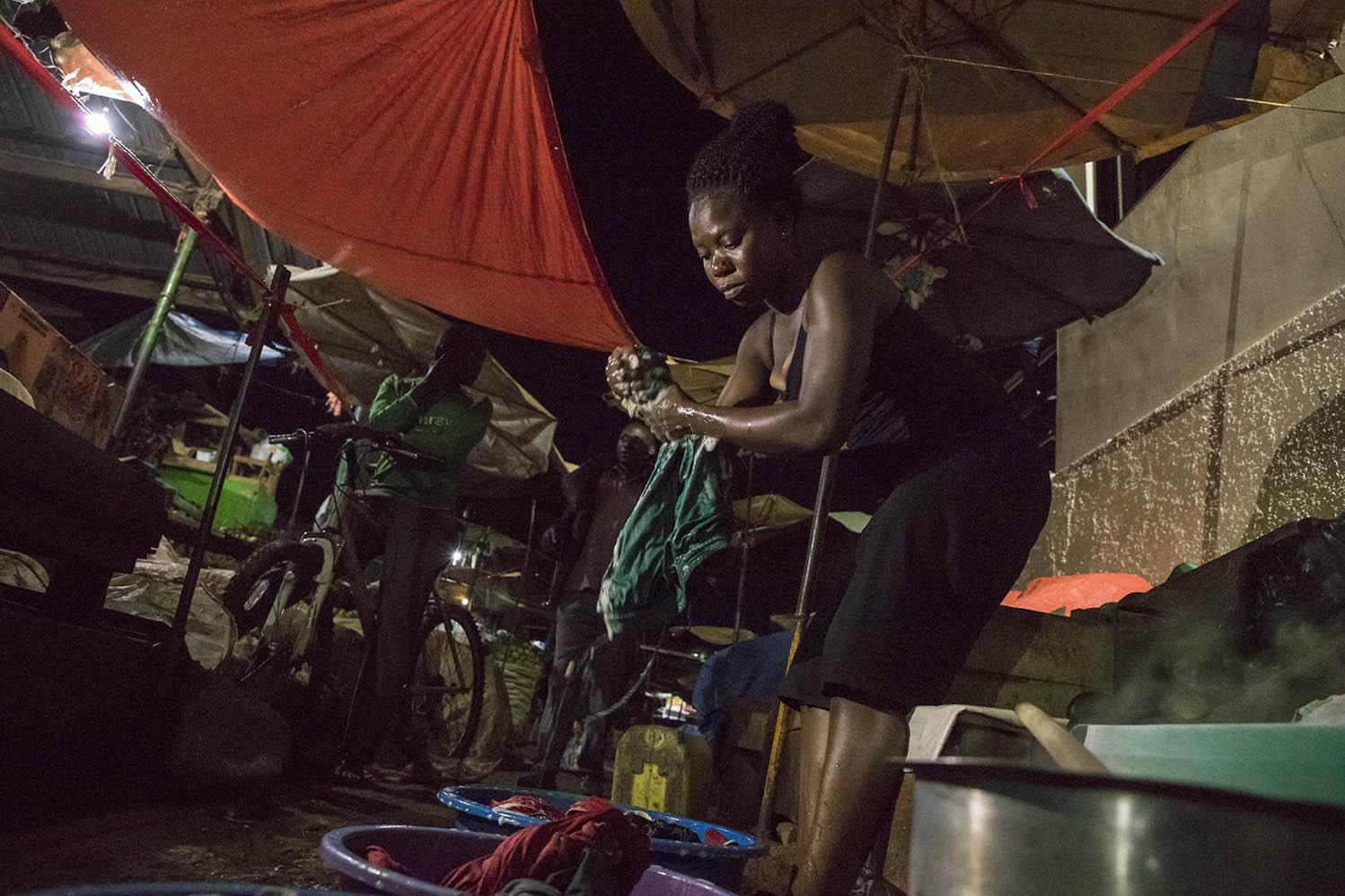 A woman washing her clothes along a walkway in the Nakawa Market after spending four days away from home.