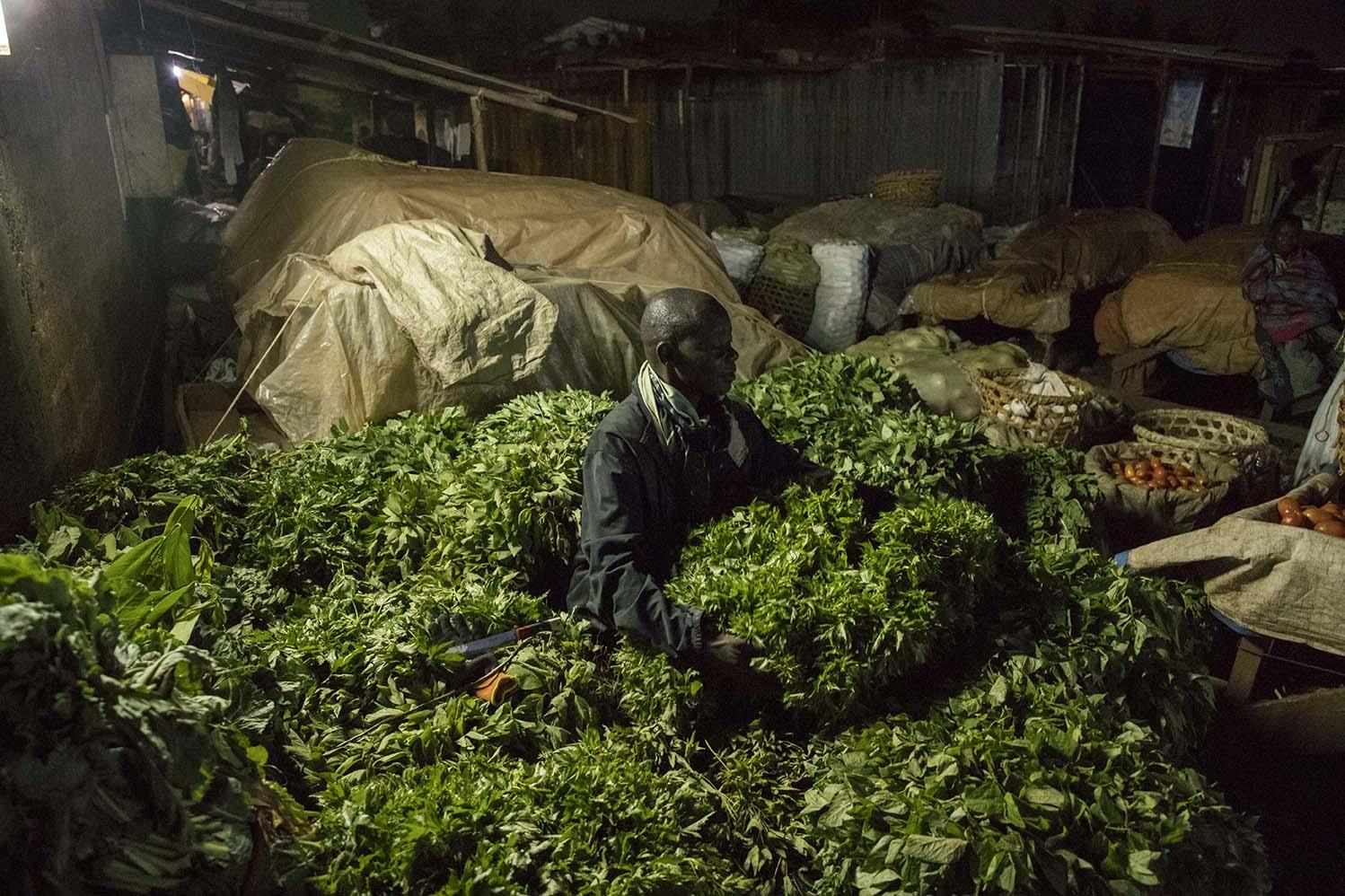 Moses Onen (42), a Nakawa Market vendor, counts bundles of greens to sell in the morning. Food delivery trucks were one of the few vehicles exempted from the driving ban by the Ugandan government. They were allowed to operate during the night since they were essential for delivering food into Kampala.