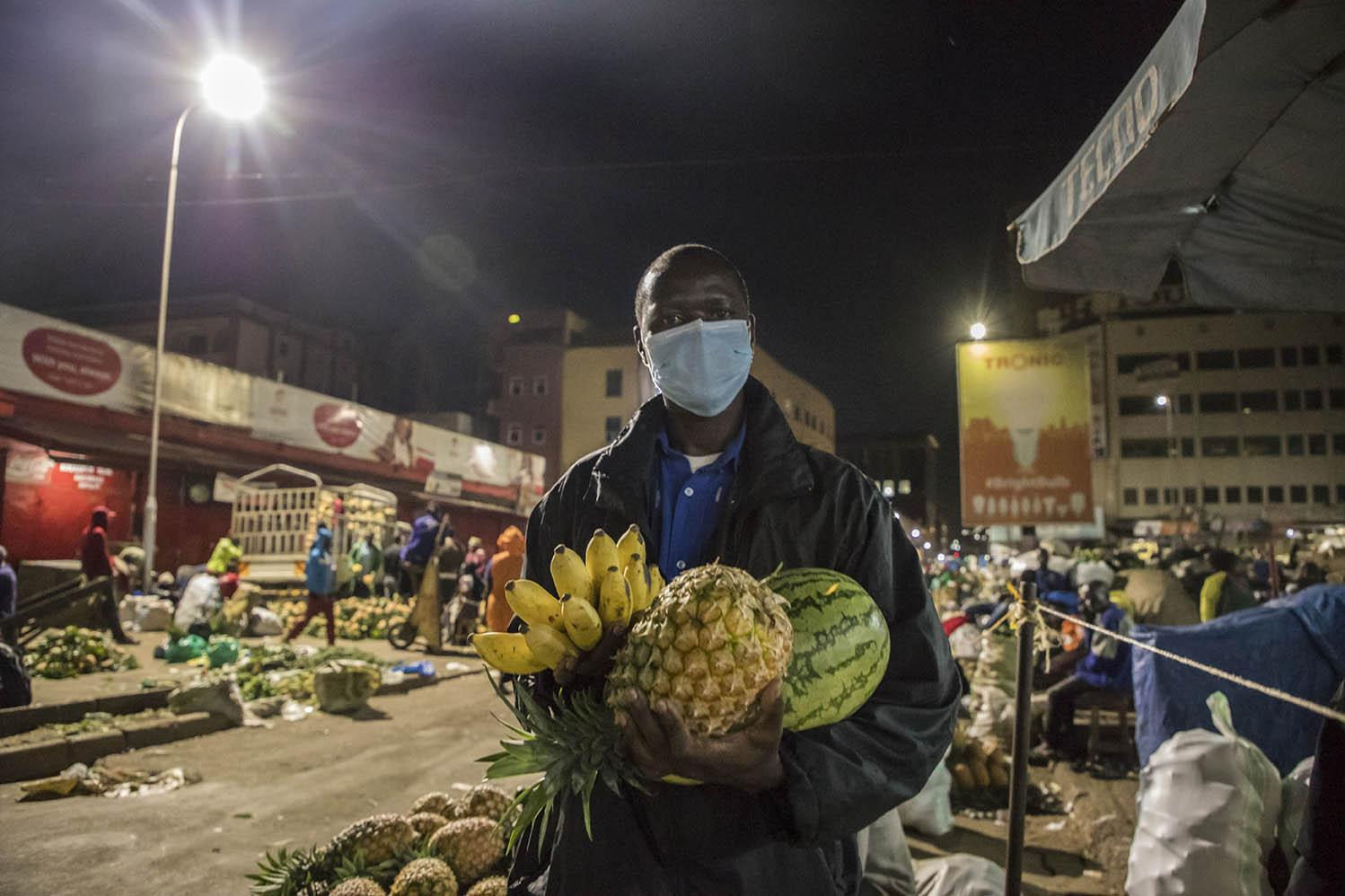 Charles Ongom, a security guard of Nakasero Market, buys fruit before his night shift on 10 April 2020. Security was heavily deployed in most of the markets in Kampala to ensure that vendors and their property are safe in the night.