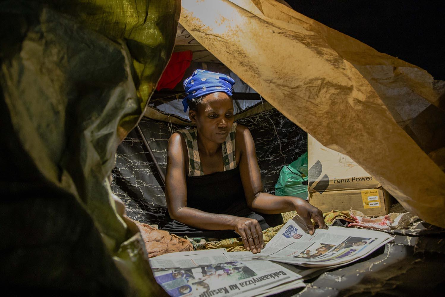 Gertrude (45), a Nakawa Market vendor, reads a newspaper in a self-made tent where she spends her nights on 9 April 2020. She decided to stay at the market and sell vegetables so she can continue sending money to her five children back at home.