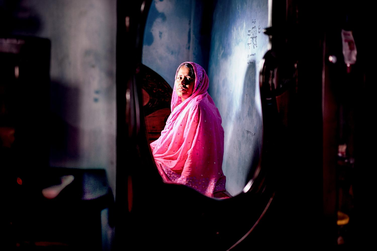 "Portrait of textile worker Morzina Begum (40) inside her house. Tongi, Bangladesh. She has been fighting against sexual violence for textile workers for decade and later dismissed from her job. ""I was dismissed from my job not because of Corona Virus, or order cancellation. It's because I was voicing for worker's right, I wanted to give justice to female Textile workers who were routinely facing abuse and injustice"". Tongi, Bangladesh"
