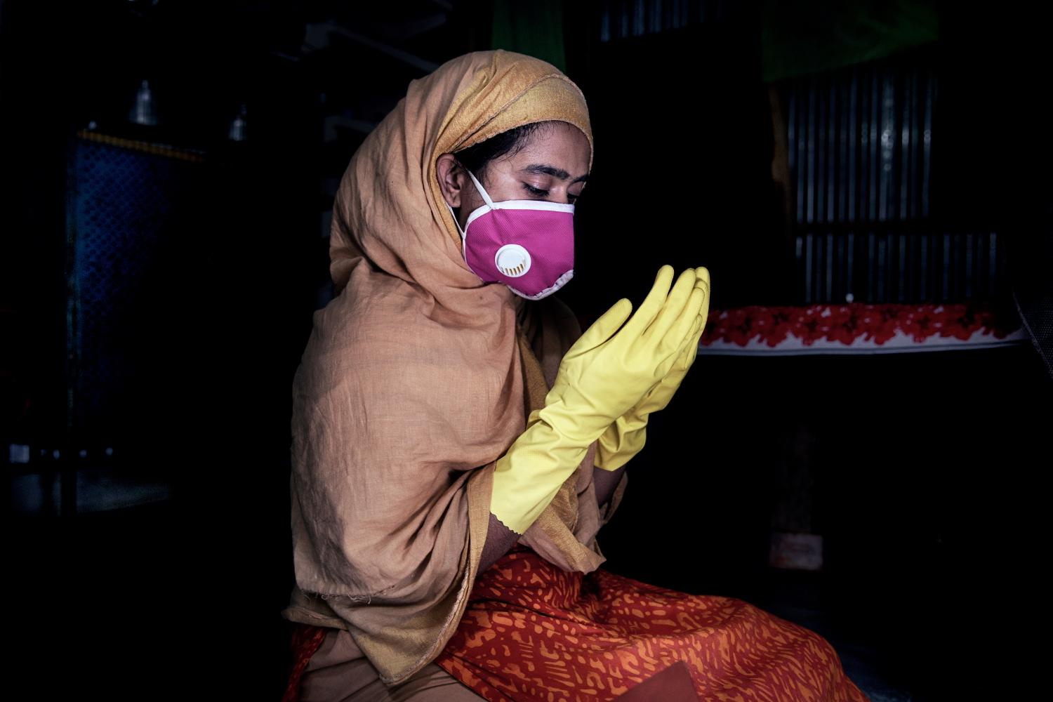 "21 years old, Textile worker Pinky s praying inside her room who has been abused by her husband and left alone with her son.""There was no one to help me when my husband tortured me every night. It was intolerable but I could not report to my factory. I did not want to lose my job"". Korail Slum, Dhaka, Bangladesh"