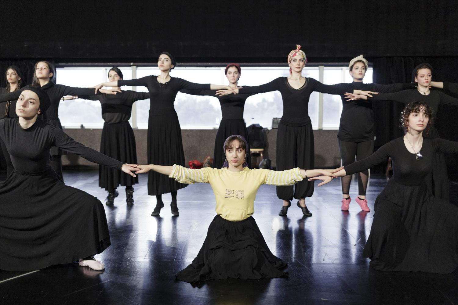 The crew rehearses for a show which got cancelled shortly before the premiere. A video of the dance rehearsals went viral on iranian media, which bashed the show. While rehearsing in Iranian public facilities, women have to wear wide, long and dark clothes.