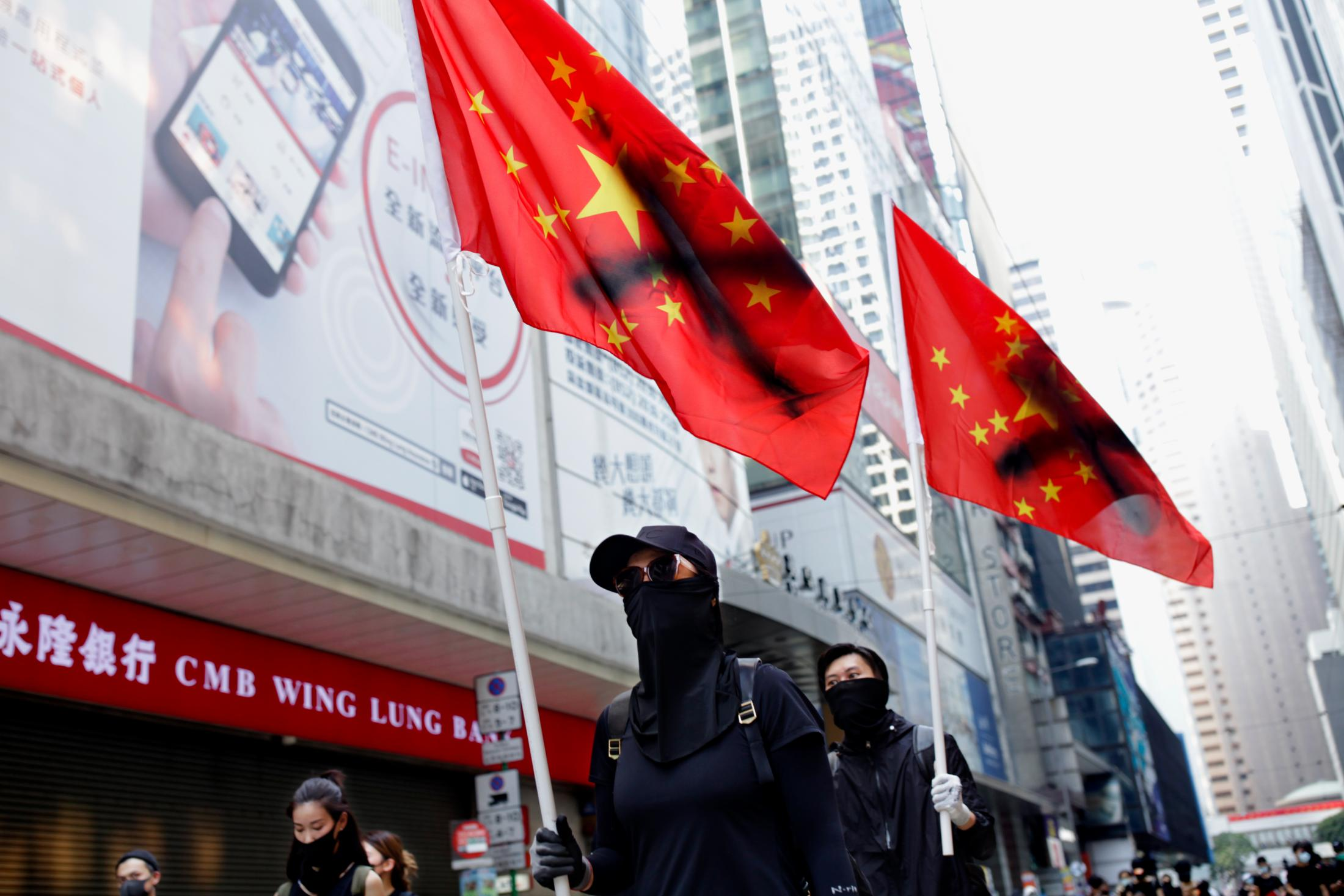 Two protesters carry flags of the People's Republic of China, with a painted X, on the 70th anniversary of the Chinese Communist Party in an unauthorized march.
