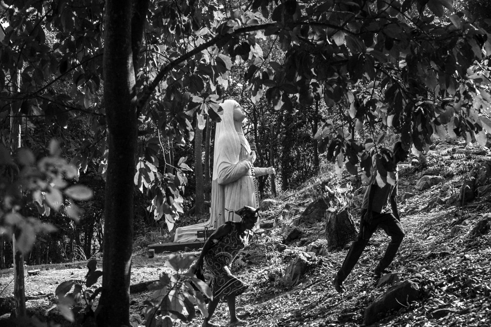 Pilgrims climb a hill to the statue of Maria, mother of Jesus, the centerpiece of worship at the Our Lady of Lourdes grotto.