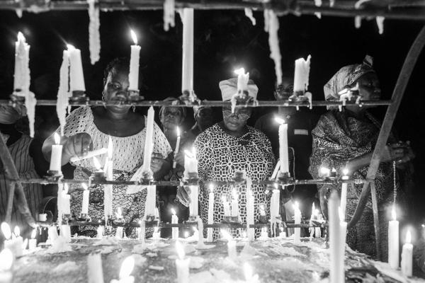 Women light their candle at an altar at the Our Lady of Lourdes grotto.