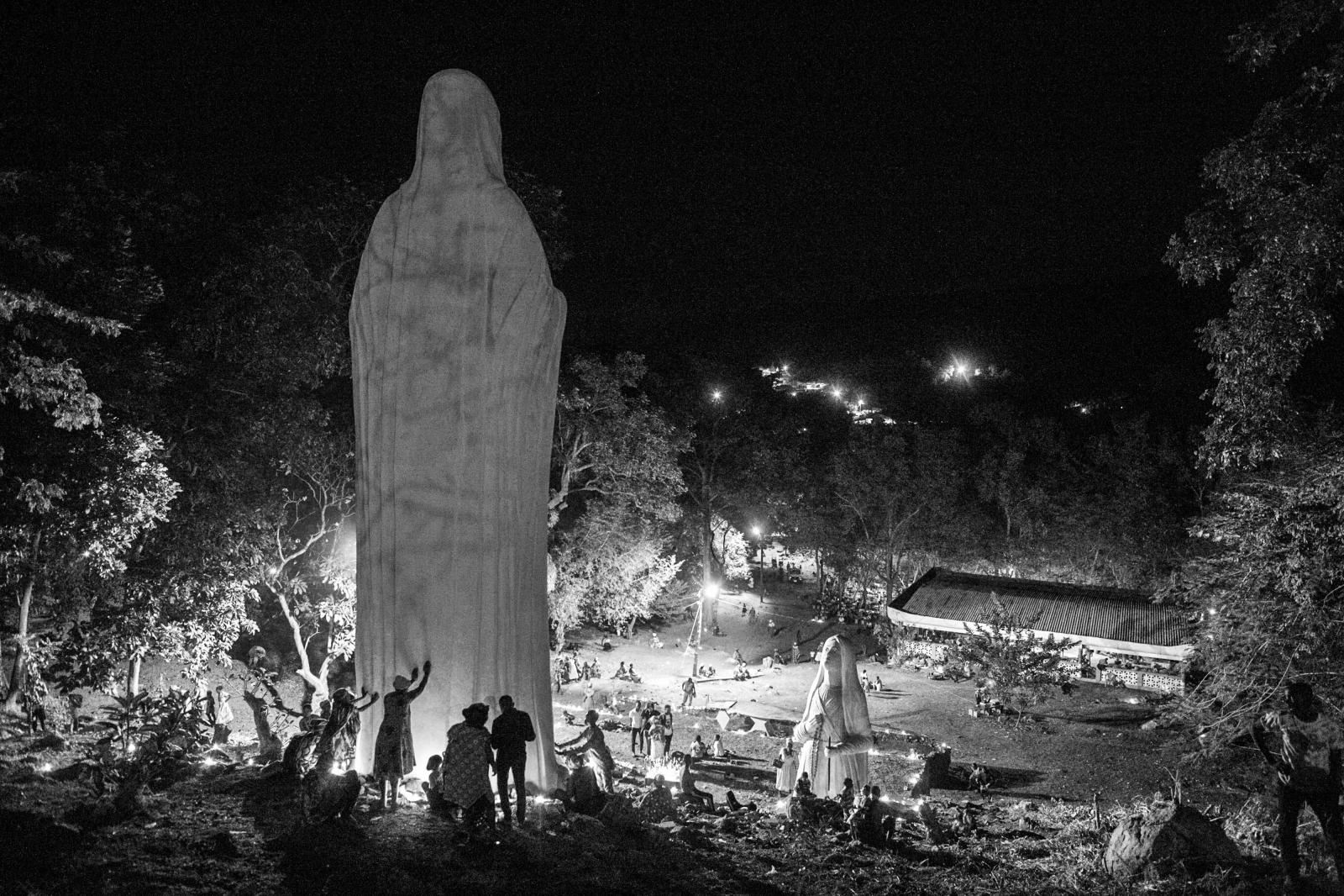 Pilgrims touch a giant statue of Maria to pray, the mother of Jesus the centrepiece of worship at the Our Lady of Lourdes grotto.