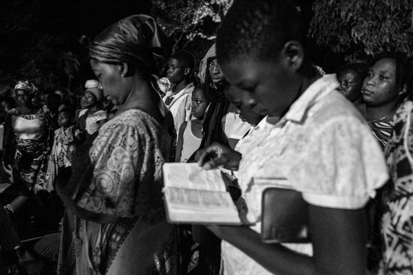 A young woman reads the bible at the Our Lady of Lourdes grotto.