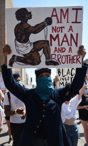 """Marvin-Alanzo Greer holds up a sign as he marches in the Protest Against Police Murder on Sunday, June 7, 2020, on Tucker Blvd. in St. Louis. Demonstrators marched in leau of the deaths of Black lives at the hands of police officers including Breonna Taylor, Ahmaud Arbery and George Floyd. """"No justice, no peace,"""" chanted the protestors."""