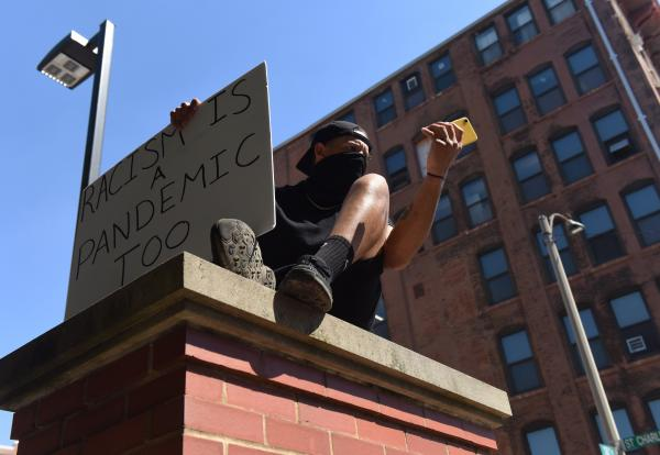 """A protestor sits above the crowd marching down 18th St. at the Protest Against Police Murder on Sunday, June 7, 2020, in St. Louis. Protestors were encouraged to wear masks during the demonstrations because of the COVID-19 pandemic. """"We will persist through all circumstances,"""" shouted the protestor from the ledge."""