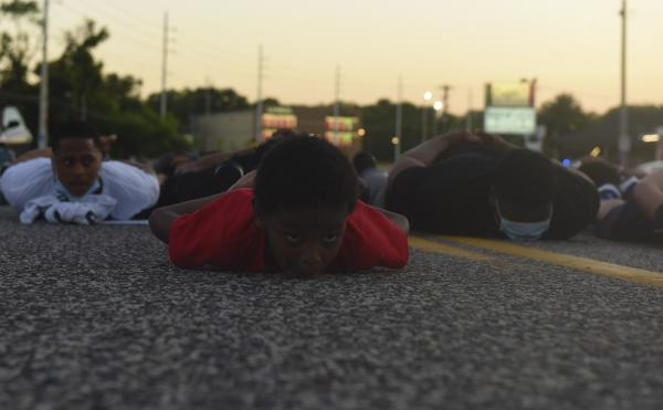 """Blue Scott, 6, lays on the pavement outside the Florissant Police Department for 8 minutes and 46 seconds on Sunday, June 7, 2020, on Lindberg Blvd. in Florissant. The demonstration symbolized the amount of time former Minneapolis Police Officer Derek Chauvin knelt on George Floyd's neck. """"I want to do more,"""" said Blue said. """"He should not have died like that."""""""