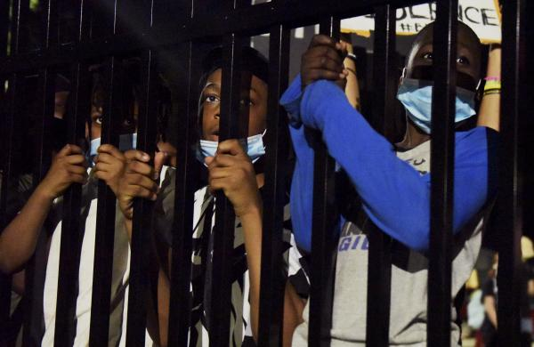 """Three boys look through the fence seperating protestors from the Florissant Police Department on Sunday, June 7, 2020. """"I am scared of [the police],"""" said one of the children."""