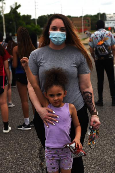 """Crystal Howard holds her daughter Nyra Hall, 5, in front of the Florissant Police Department, on Sunday, June 7, 2020. """"I will always stand with her,"""" said Howard. """"I don't want her to grow up living in fear. No child should live with that fear of 'am I next?'"""""""