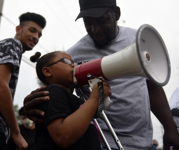 """Bishop Derrick Robinson, an organizer for 'Respect Us,' encourages Tay'Jah Jones, 9, to speak at a protest on Sunday, June 7, 2020, at the Florissant Police Department. """"We need to amplify black voices,"""" said Robinson."""