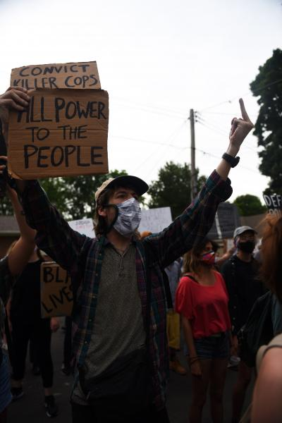 """A protestor raises his middle finger towards police guarding Florissant Mayor Tim Lowrey's home on Monday, June 8, 2020. Demonstrators walked from the Police Department to the Mayor's home to demand the prosecution and convition of former Florissant Police Detective Joshua Smith. """"We will apply pressure,"""" said protest organizer Bishop Derrick Robinson."""