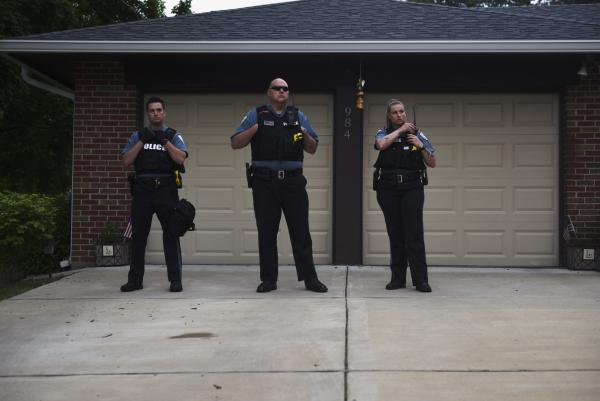 Police officers guard Florissant Mayor Tim Lowrey's home as protestors demand the indictment and conviction of former police detective Joshua Smith on June 8, 2020. Smith had been caught on video hitting a suspect with his unmarked SUV, followed a beating outside of the officer's jurisdiction.
