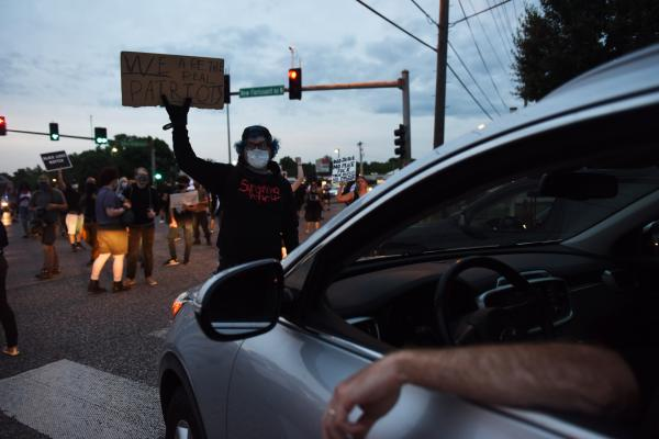 """A man blocks a car as protestors hold an intersection during a march on Lindberg Blvd. in Florissant, Missouri on Monday, June 8, 2020. """"Whose streets? Our Streets!"""" chanted protestors."""