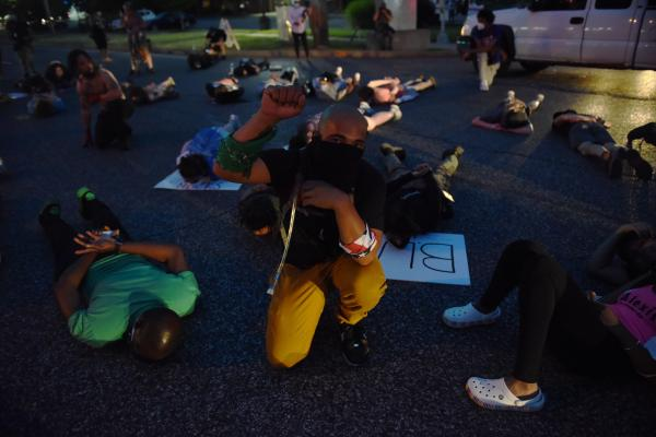 A protestor kneels in the middle of a die-in demonstration on Lindberg Blvd. in Florissant, Missouri, on Monday, June 8, 2020.