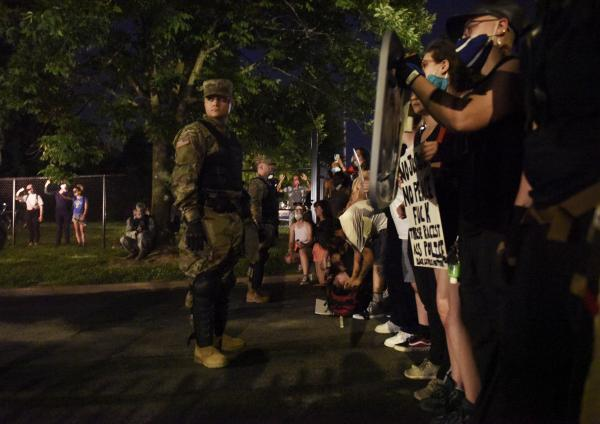 A member of the Army National Guard looks to his commanding officer as demonstrators line the gate to the Florissant Police Department on Monday, June 8, 2020. Police officers declared demonstration an unlawful assembally and threatened to arrest protestors and use chemical munitions if they did not disperse.
