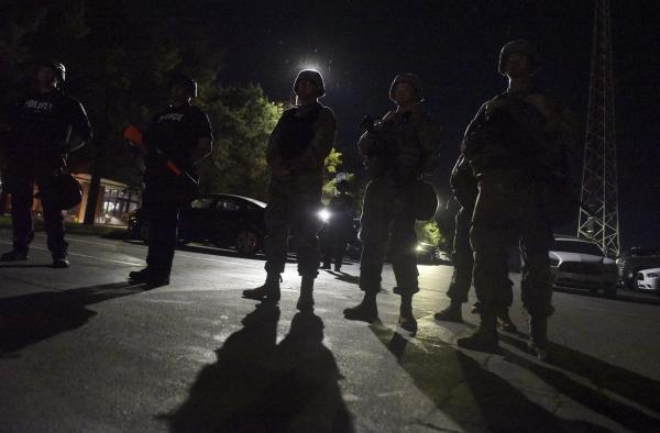 Army National Guard members guard the Florissant Police Department as demonstrators line the gate on Sunday, June 7, 2020.