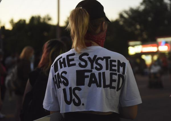 A protestor wears a t-shirt that reads 'The system has failed us' on Monday, June 8, 2020 while a demonstration blocks traffic on Lindberg, Blvd. in Florissant, Missouri. Demonstrators refer to topics including red-lining, the school-to-prison pipeline, police brutaility and racial profiling.