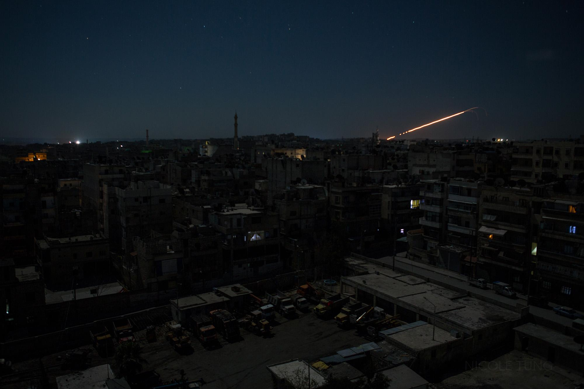 A trail of light follows a rocket launch from a government held area of Aleppo, Syria. March 2013.