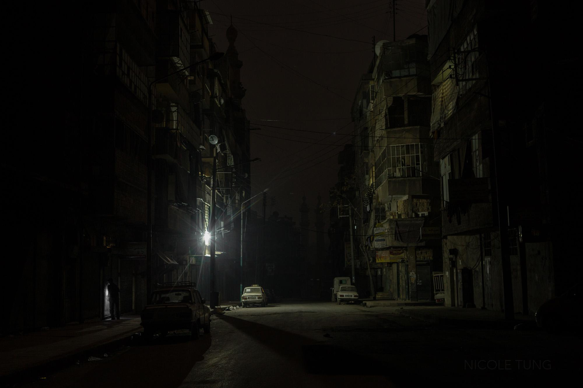 A light, running off a generator, brightens a street near the frontline of Salaheddin neighborhood of Aleppo, Syria. March 2013.