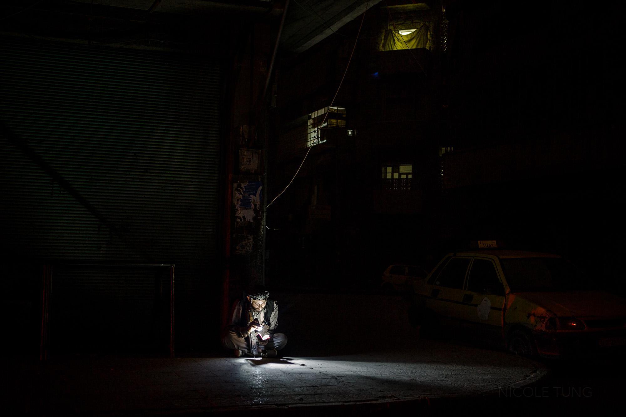 A jihadi fighter, sitting on a street corner, reads the Qur'an using a flashlight in Bustan Al Qasr, Aleppo, Syria. March 2013.