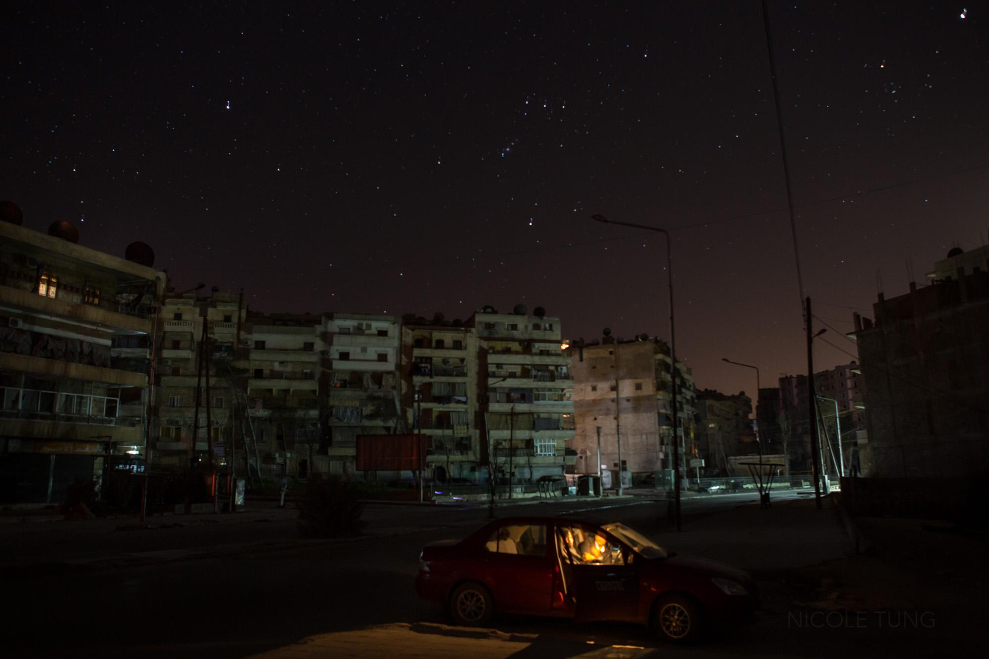 Two people are lit by the interior car light in a residential neighborhood of Aleppo, Syria. March 2013.