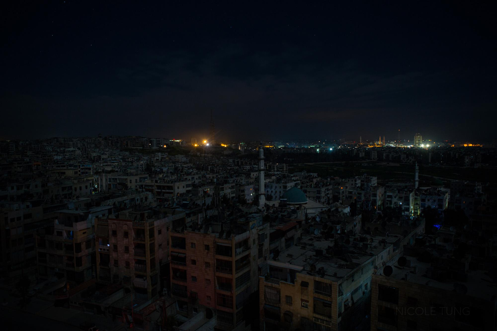 Opposition-held Aleppo, foreground, is seen against a brightly lit government held area in the horizon. Aleppo, Syria. March 2013.