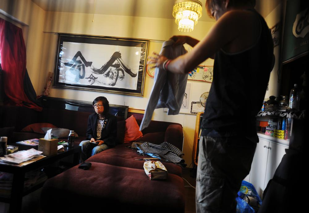 Takaki Hara (38), right, checks and folds his son's jacket while his son, Rukiya(12 ),left, watches TV just before going out together to attend the lecture and report on Takaki Hara's single father family NPO activities' lecture for college students. July 21, 2011.