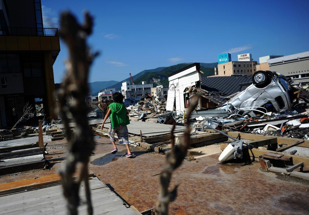 Rukiya Hara (12) meanders amid the ruins of Ofunato city, Iwate prefecture which was destroyed by the 3.11 M9 earthquake and tsunami. He and his father, Takaki Hara (38) are on the way to the Tohoku region where the 3.11's M9 earthquake and Tsunami devastated for volunteering and research on the newly displaced single parent families due to the 3.11 earthquake as part of Takaki Hara's NPO and personal mission. June 11, 2011.
