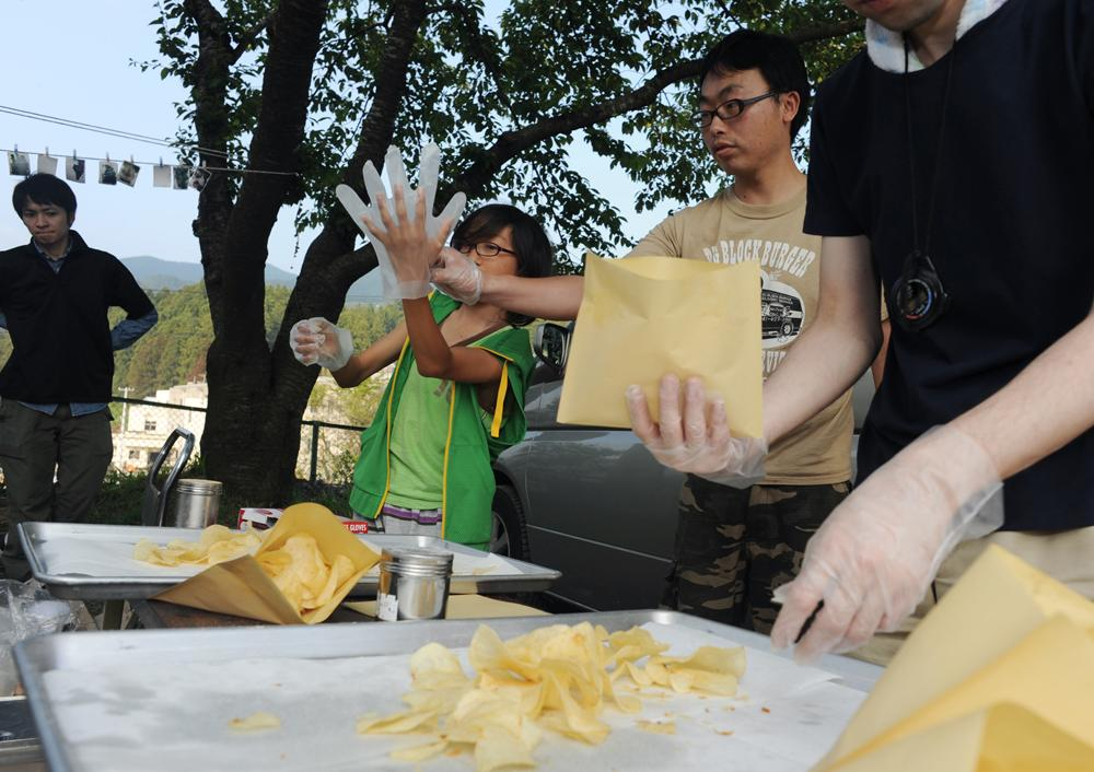Rukiya Hara (12) helps making potato chips for the evacuee from 3.11 earthquake and tsunami with the help of other volunteers at Akasaki district community center, Iwate prefecture. June 11, 2011
