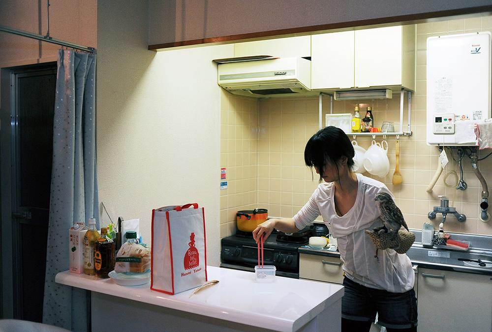"Mariko Nakano, 29, feeds her pet owl ""Maru-Roundishness in Japanese"" a frozen quail in a kitchen. 2013, Koto-ku, Tokyo, Japan."
