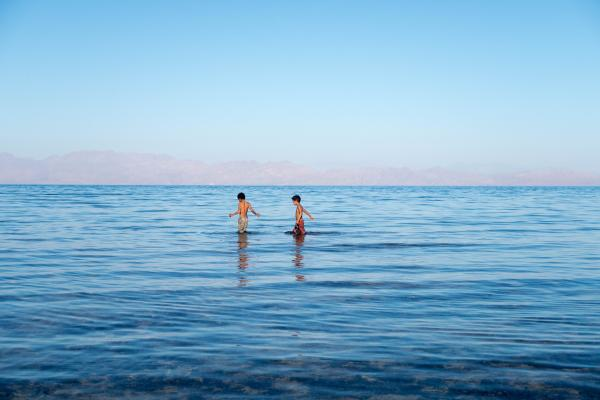 Dahab, South Sinai, Egypt  Two young boys fish off shore of the South Sinai Egyptian Red Sea.  Dahab is a small town on the southeast coast of the Sinai Peninsula in Egypt, approximately 80 km northeast of Sharm el-Sheikh. Formerly a Bedouin fishing village, Dahab is now considered to be one of Sinai's most treasured diving destinations.